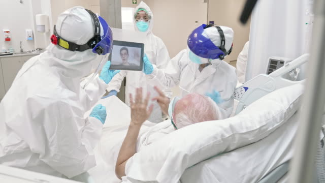 Senior man recovering from Covid-19 having a video call with his grandson at the hospital ICU
