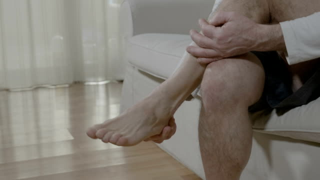 Senior man relaxing and massaging his tired foot at home sitting on couch Senior man relaxing and massaging his tired foot at home sitting on couch pain stock videos & royalty-free footage