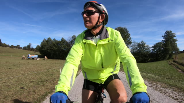 Senior Man Relaxing Cycling on Countryside