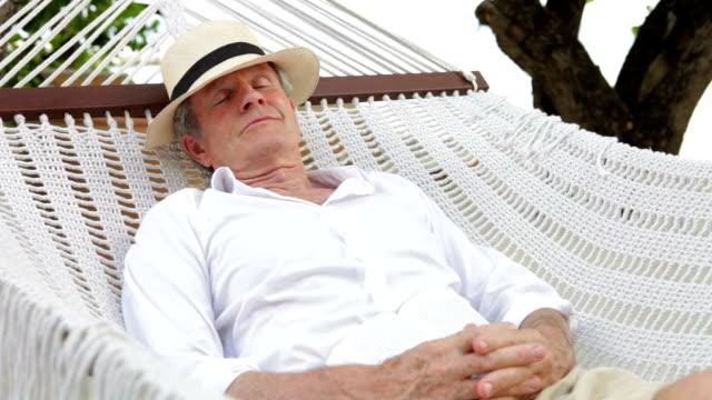 Senior Man Relaxing In Beach Hammock video