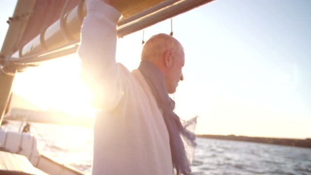 Senior man relaxing on his leisure yacht in the sunset video