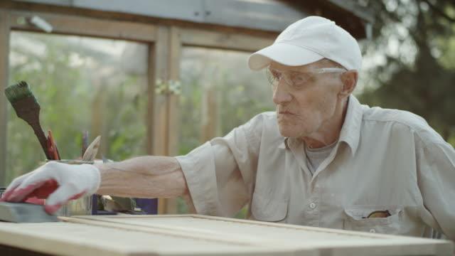 Senior homme, rénovation de vieux meubles - Vidéo