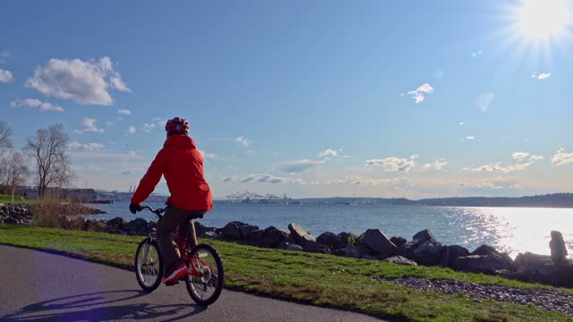 Senior man riding bike on Seattle waterfront trail with bright sun behind video