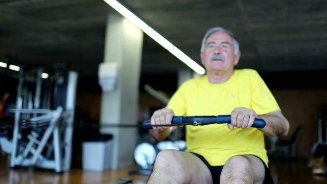 senior mannes rudern im fitnessraum - männliches tier stock-videos und b-roll-filmmaterial