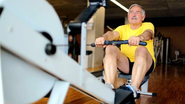 Senior man rowing at the gym video