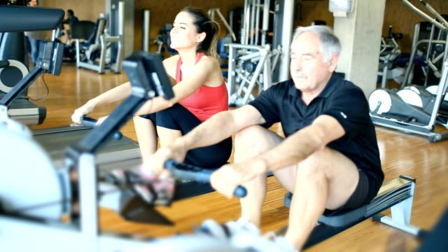 Senior man rowing at the gym with his instructor video