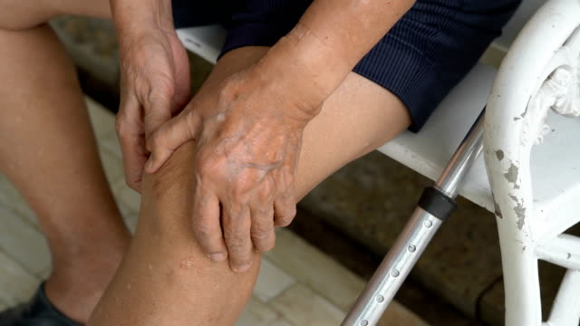 CU Senior man rubbing his knee Close-up shot of senior man rubbing his knee knee stock videos & royalty-free footage