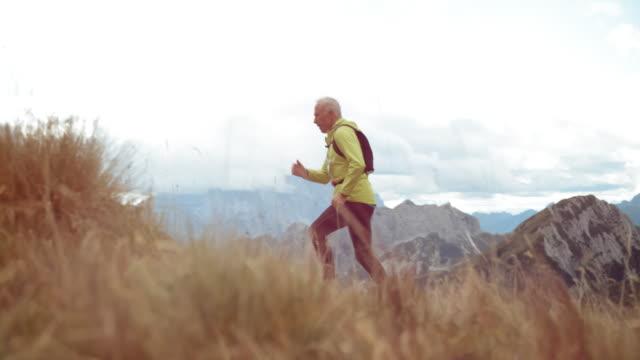 slo mo ds senior man running a marathon up a mountain meadow - siła filmów i materiałów b-roll