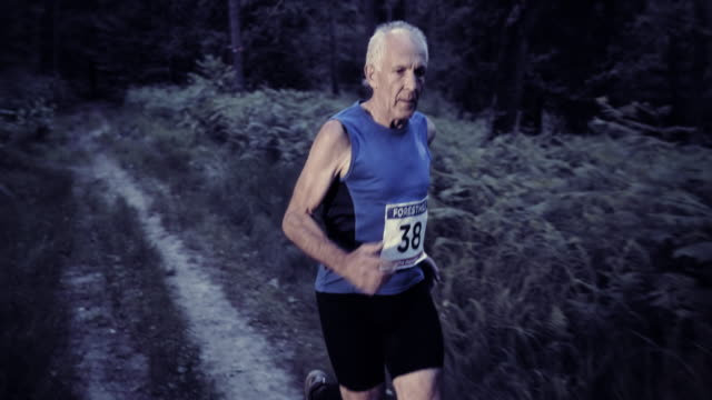 SLO MO DS Senior man running a trail marathon at sunset video
