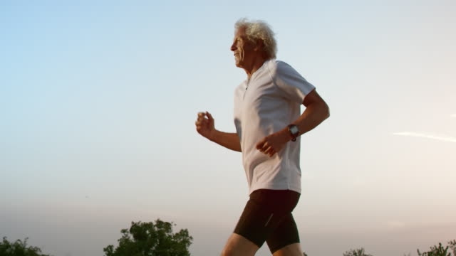 SLO MO TS Senior man running at sunset video