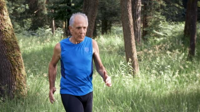 SLO MO Senior man running through the forest video
