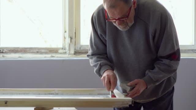 vídeos de stock e filmes b-roll de senior man sanding old window frame in his apartment - old men window