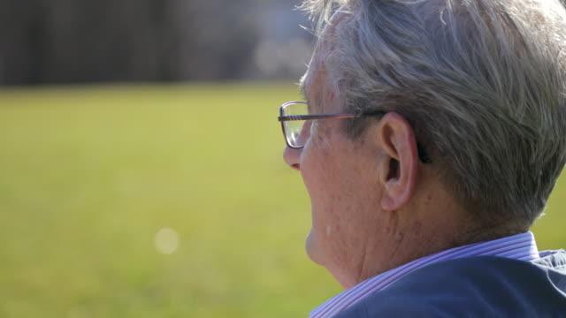 年配の男性 (土) 単独でフィールドの距離に探して - ベンチ点の映像素材/bロール