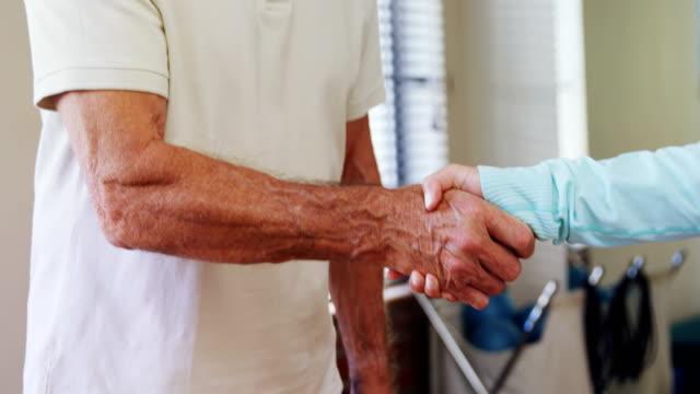 Senior man shaking hand with physiotherapist 4k video