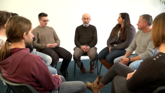 vídeos y material grabado en eventos de stock de 4k dolly: hombre senior en el círculo del grupo de apoyo - servicios sociales