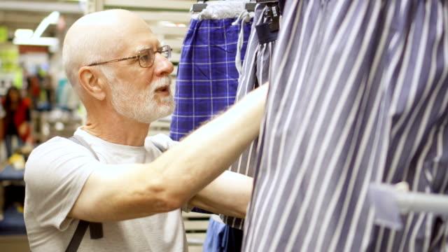 vidéos et rushes de senior homme shopping mall. gars barbu chauve debout près des étagères avec des vêtements en choisissant des sous-vêtements - homme slip