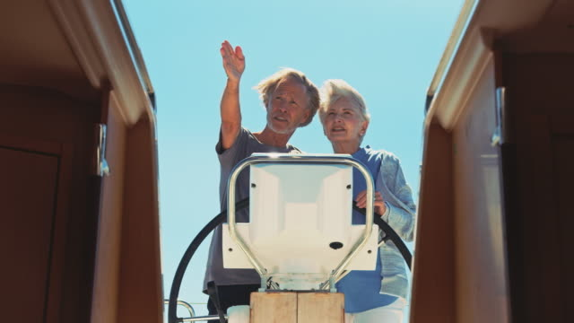 Senior man showing direction to woman in yacht Handheld shot of man showing direction to woman while steering boat. Senior couple traveling in yacht during summer. They are spending leisure time together. guidance stock videos & royalty-free footage