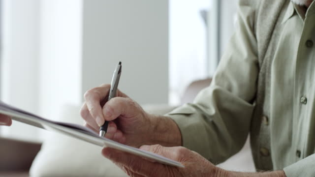 Senior man signing financial papers Senior man signing financial papers in livingroom salesman stock videos & royalty-free footage