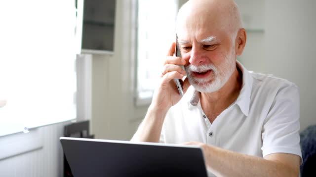 Último homem sentado em casa com laptop e smartphone. Usando o celular, discutindo o projeto em tela - vídeo