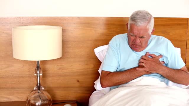 vídeos de stock e filmes b-roll de idoso sentado na cama, tendo um ataque cardíaco - ataque cardíaco