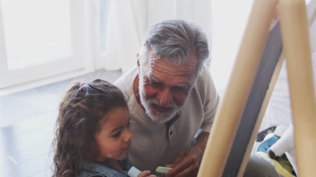 Senior man sitting on the floor drawing with his granddaughter on a blackboard, elevated view Senior man sitting on the floor drawing with his granddaughter on a blackboard, elevated view granddaughter stock videos & royalty-free footage