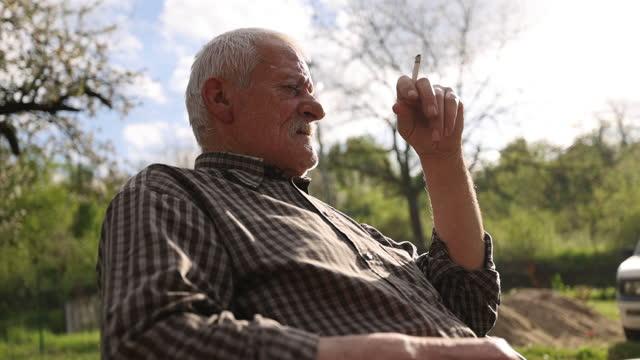 Senior man sitting, relaxing and smoking in backyard video