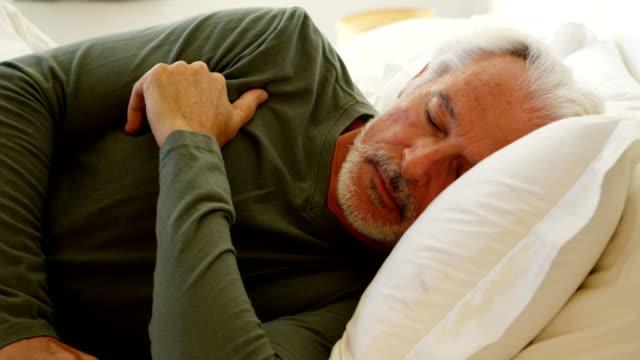 Senior man sleeping on bed in bedroom 4k Senior man sleeping on bed in bedroom at home 4k man sleeping stock videos & royalty-free footage