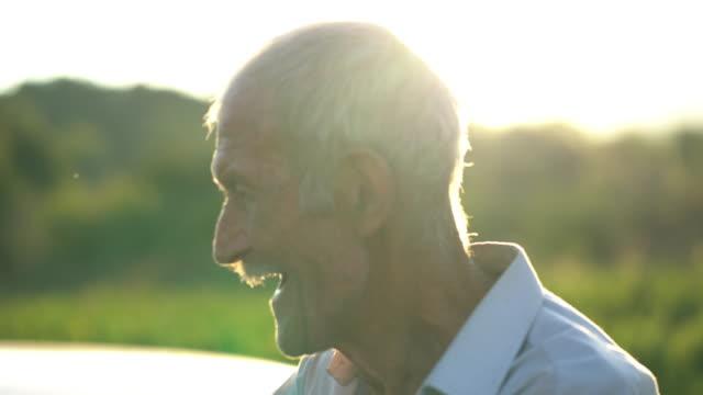 先輩男性は笑顔で、美しい晴れた日に彼のラズベリーのプランテージを見て彼の時間を過ごす - disruptagingcollection点の映像素材/bロール