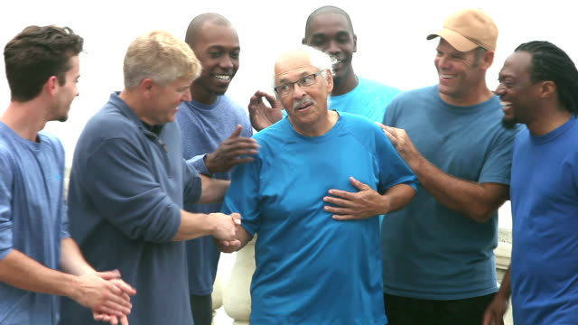 Senior man standing, friends gather round and smile video