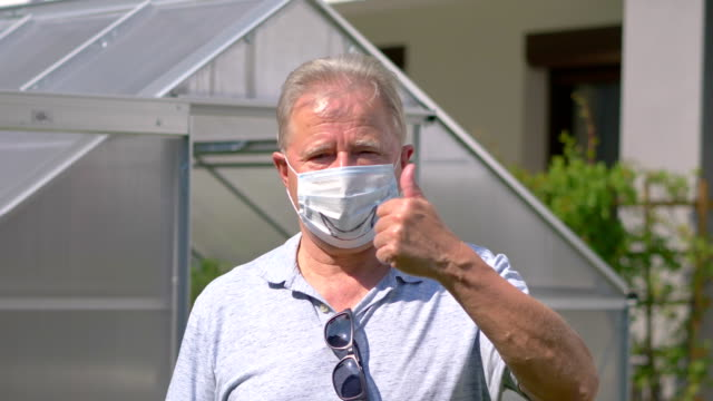 Senior man standing in the garden in face mask and showing ok during pandemic time in 4K Slow motion 60fps video