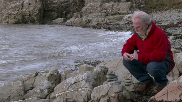 Senior man stone staking on a rocky shore 4K footage shot at 50fps and interpreted at 25fps to give a slower motion dumfries and galloway stock videos & royalty-free footage