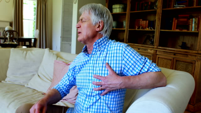Senior man suffering from chest pain in living room video