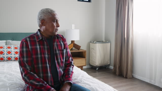vídeos de stock e filmes b-roll de senior man suffering with depression sitting in bedroom at home - shot in slow motion - alzheimer