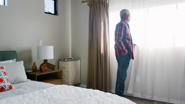 vídeos de stock e filmes b-roll de senior man suffering with depression standing by bedroom window at home - shot in slow motion - old men window