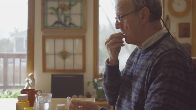 Senior man takes medication Close up of senior man taking his prescription medication painkiller stock videos & royalty-free footage
