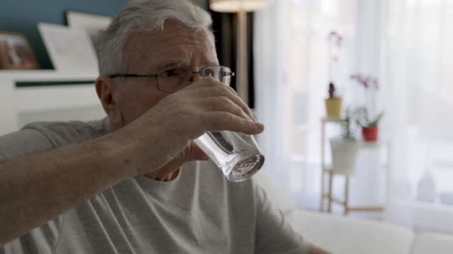 Senior Man Takes Medications At Home Serious senior man in sitting on sofa in living room takes daily vitamins or diet supplements or prescription medicine. painkiller stock videos & royalty-free footage