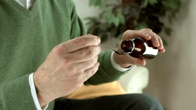 hd: uomo anziano assunzione di sciroppo - sciroppo video stock e b–roll