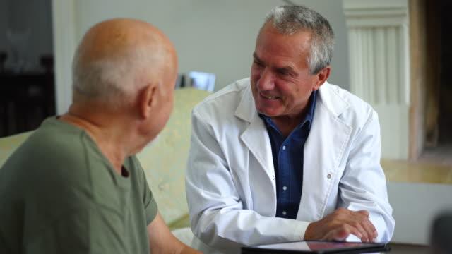 huzurevinde ki kanepede doktorla konuşan kıdemli adam - konuşmak stok videoları ve detay görüntü çekimi