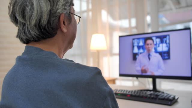 starszy mężczyzna rozmawia z lekarzami omawiając plan leczenia pacjenta podczas wideokonferencji. starszy mężczyzna rozmawia ze swoim lekarzem za pośrednictwem czatu wideo. senior technology, lifestyle, ludzie, global, emerytura, wideokonferencji, ed - dbałość o ciało filmów i materiałów b-roll