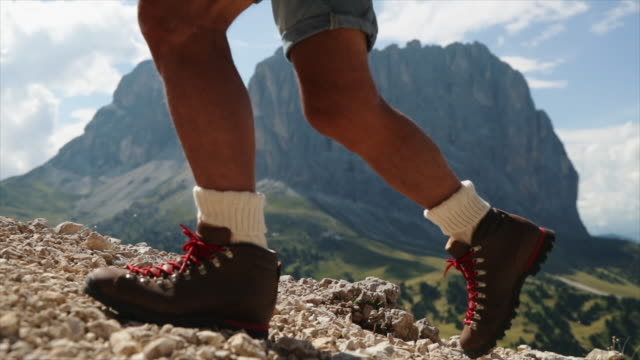 Senior man trail hiking on the Dolomites: boots close up video