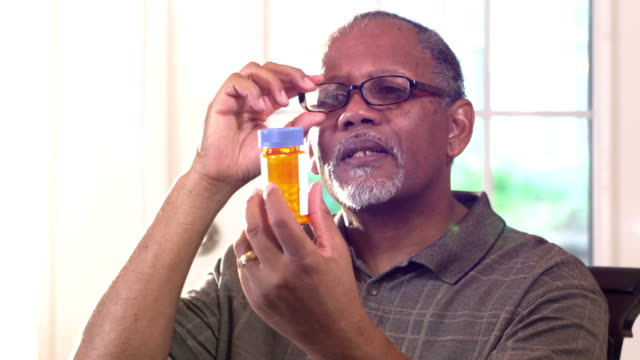Senior man trying to read prescription bottle label A senior African-American man trying to read the label on a bottle of prescription medicine. He is holding the bottle up, adjusting his reading glasses. pill bottle stock videos & royalty-free footage