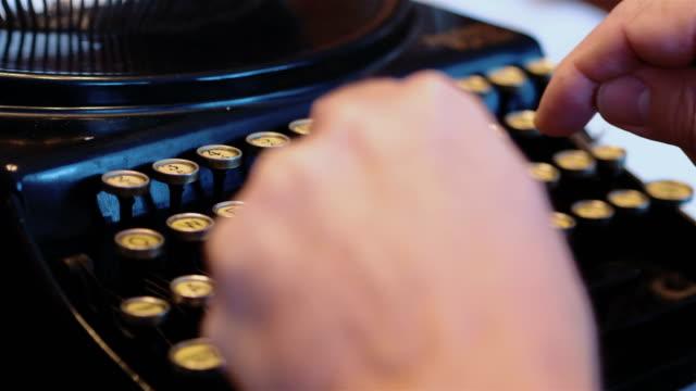 Senior man typing on an old typewriter in 4k slow motion video