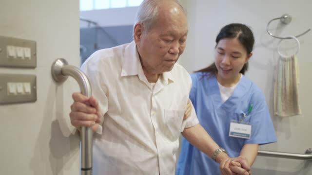 vídeos y material grabado en eventos de stock de senior man use el reposabrazos resbaladizo de seguridad en el inodoro con asistente de enfermería - manija