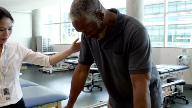 vídeos de stock e filmes b-roll de senior man uses parallel bars in rehab center - enfarte