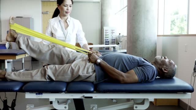 vídeos de stock e filmes b-roll de senior man uses resistance band during physical therapy session - enfarte