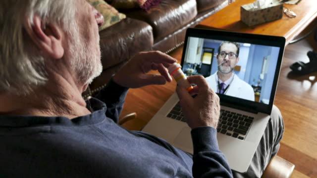 彼の医者との遠隔医療の予約のためにコンピュータを使用している先輩男性 - 処方箋点の映像素材/bロール