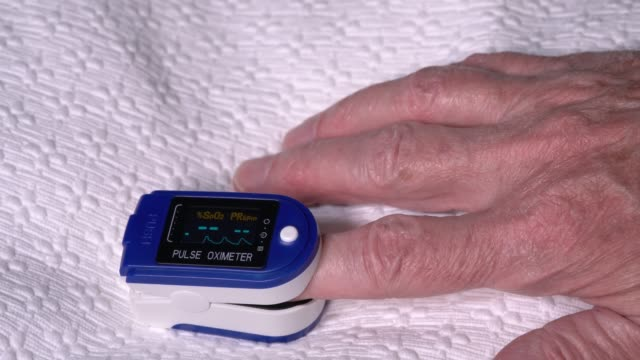 Senior man using a pulse oximeter on finger to test blood oxygen level - video