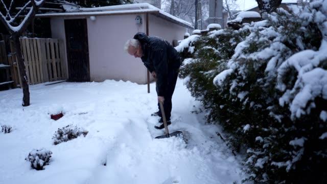 äldre man med en snöskyffel i en gårdsplanen - skyffel bildbanksvideor och videomaterial från bakom kulisserna