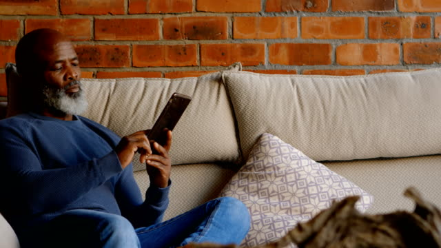 senior man using digital tablet in living room 4k - cinquantenne video stock e b–roll