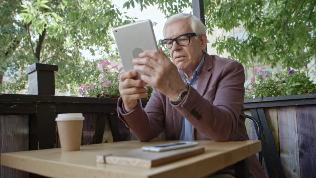 Senior Man Using Digital Tablet in Outdoor Cafe video